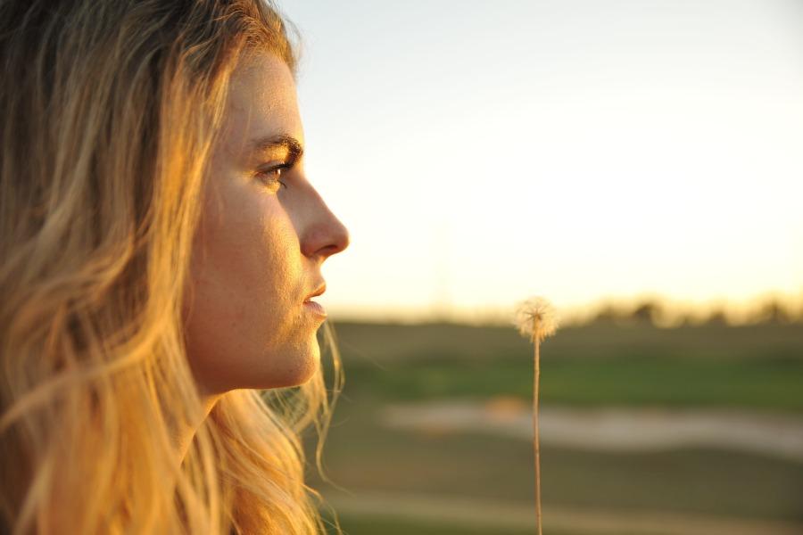 foto van een vrouw die opzij naar een paardenbloem kijkt